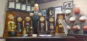 Tarleton athletic director and men's basketball head coach Lonn Reisman displays the assortment of NCAA Division II and Lone Star Conference trophies won by Tarleton State athletic teams in 2014-15. He is is holding a key to the city of Stephenville, presented to him in April by Mayor Kenny Weldon.    BRAD KEITH/TheFlashToday.com